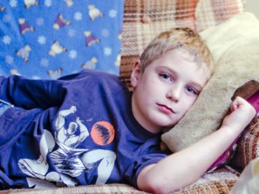 Ein Junge liegt schlapp auf dem Sofa.