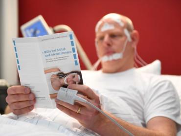 Ein verkabelter Mann liegt im Bett und liest einen Flyer des Schlaflabors.
