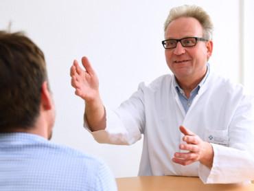 Prof. Dr. Jörg Mühling, leitender Arzt der schmerztherapeutischen Spezialambulanz, im Gespräch mit einem Patienten.