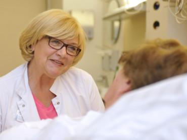 Patientenmanagerin Gaby Küster lächelt eine Patientin an, die im Bett liegt.