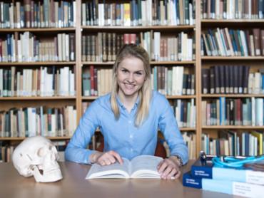 Medizinstudentin Zita Schwaibold sitzt lächeln in der Bibliothek - auf dem Tisch vor ihr liegen ein aufgeschlagenes Buch und ein menschlicher Schädel.