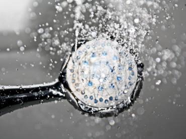 Aus einem Duschkopf fällt Wasser.