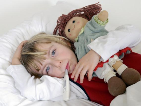 Ein krankes Mädchen liegt mit Puppe im Bett, das Fieberthermometer im Mund.