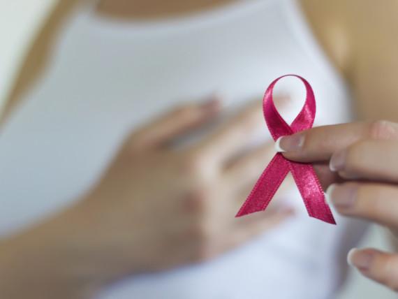 Frau hält eine rosa Schleife - ein internationales Symbol, mit dem auf die Problematik der Brustkrebserkrankung hingewiesen wird.