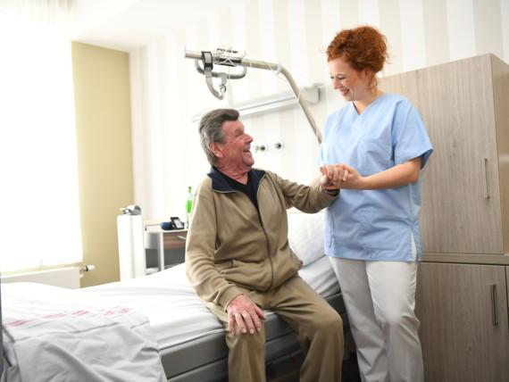 Eine Krankenpflegeschülerin hilft lächelnd einen Patienten aus dem Bett.