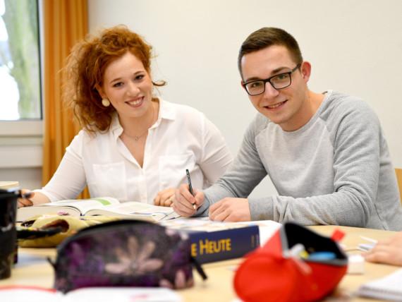 Zwei Krankenpflegeschüler sitzen lächelnd in einem Klassenraum der Bildungsakademie.
