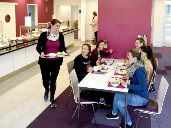 Eine Gruppe Mütter beim geselligen Mittagessen im Restaurant des Marianne van den Bosch Hauses.