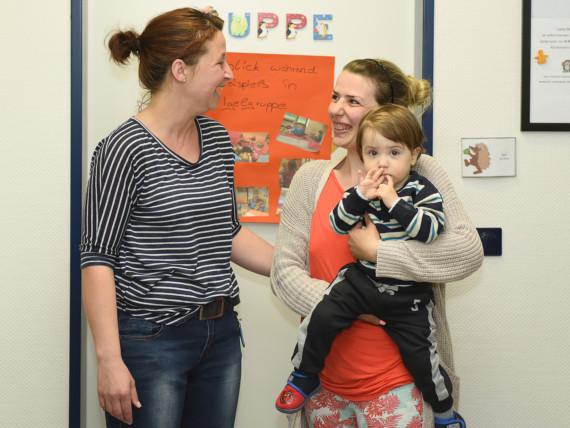 Eine Mutter und ihr Kleinkind begegnen einer Mitarbeiterin des Marianne van den Bosch Hauses lächelnd auf dem Flur.
