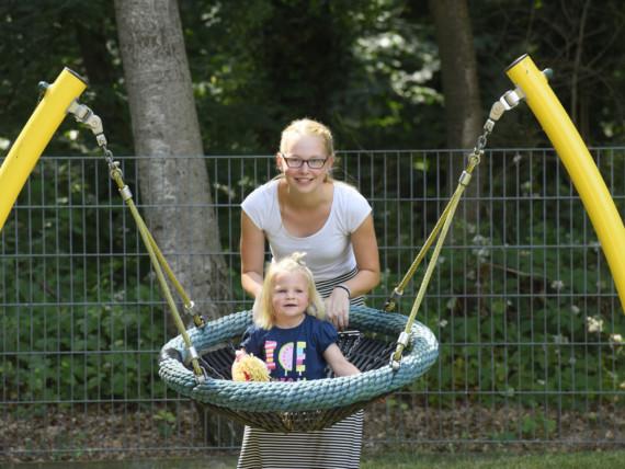 Ein Kind sitzt zufrieden in der Nestschaukel, eine lächelnde Erzieherin im Hintergrund.