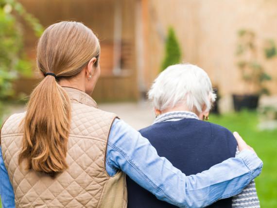 Eine junge Frau hält eine ältere Frau im Arm - Rückansicht.