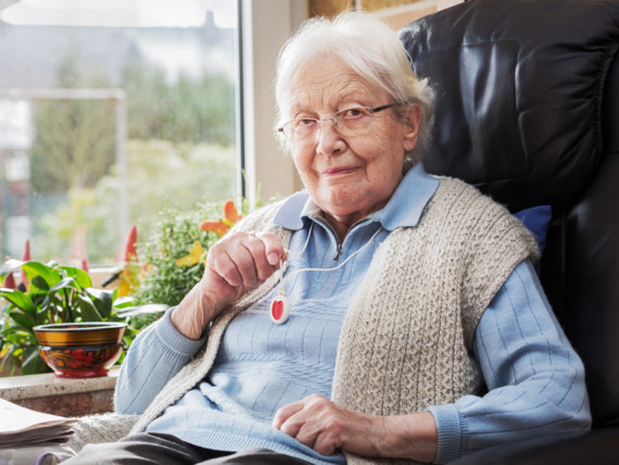 Eine Seniorin sitzt im Sessel und präsentiert den Notfallknopf des Hausnotrufs.