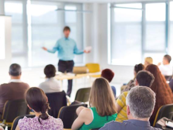Eine Seminarsituation: Der Dozent (unscharf im Hintergrund) erläutert mit ausladender Geste.