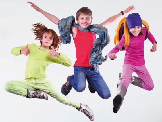 Drei Kinder - bunt gekleidet - springen lebenslustig in die Höhe.