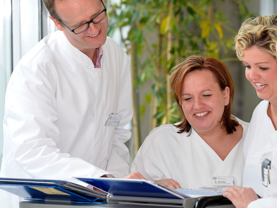 Dr. Klaus-Dieter Willenborg, Chefarzt der Klinik für Neurologie und klinische Neurophysiologie, bespricht mit zwei Kolleginnen eine Patientenakte.
