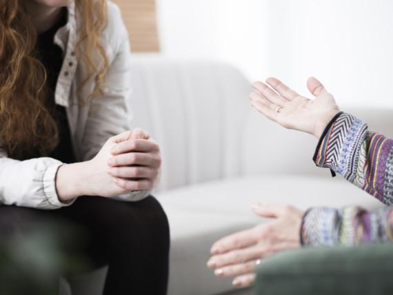 Therapeutin und Patientin sitzen sich im Gespräch gegenüber, die Gesicher sind nicht erkennbar.