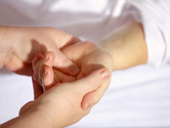 Pflegesituation: Eine junge Hand hält eine alte Hand.