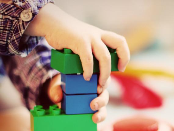 Ein Kind spielt mit farbigen Legosteinen. Man sieht nur Hände und Legosteine.