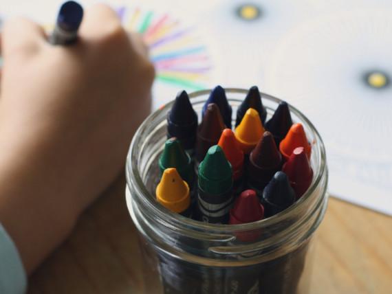Ein Kind malt mit Wachsmalstiften ein buntes Bild.
