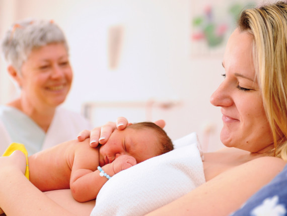Eine Mutter streichelt ihr neugeborenes Baby, das auf ihrem Bauch liegt. Im Hintergrund lächelt eine Hebamme.