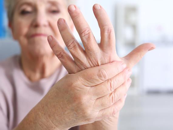 Eine Patientin hält sich die Hand vor Schmerzen.