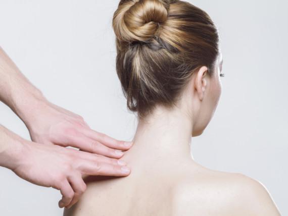 Untersuchung: Zwei Hände tasten im oberen Bereich der Wirbelsäule einer Patientin.