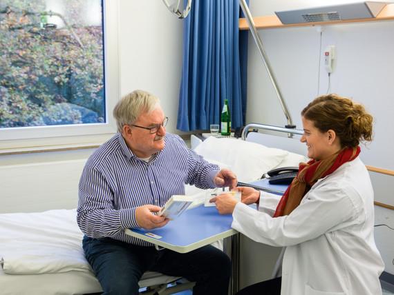 Eine Apothekerin berät einen Patienten im Krankenhaus zur Medikation.