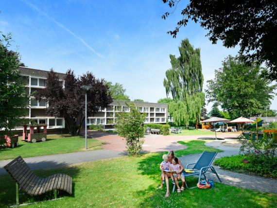 Eine Mutter sitzt mit ihren zwei Kindern vor dem Marianne van den Bosch Haus in Goch.