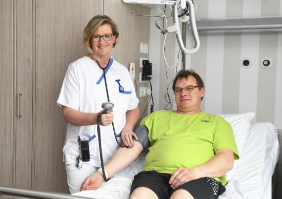 Eine Krankenschwester des Katholischen Karl-Leisner-Klinikums misst einem Patienten lächelnd den Blutdruck.
