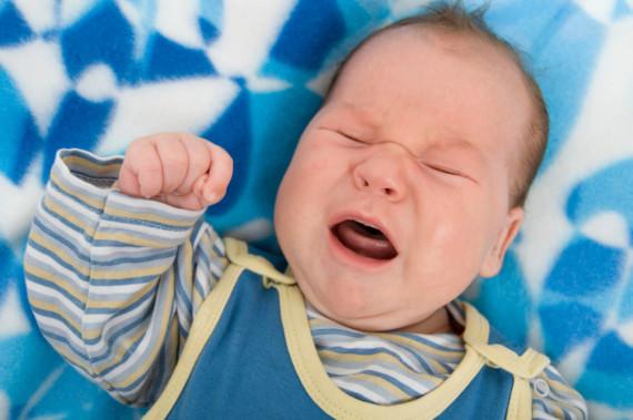 Ein Baby schreit mit geschlossenen Augen.