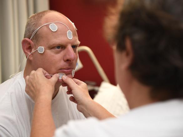 Eine Mitarbeiterin des Schlaflabors verkabelt einen Patienten für ein EKG.