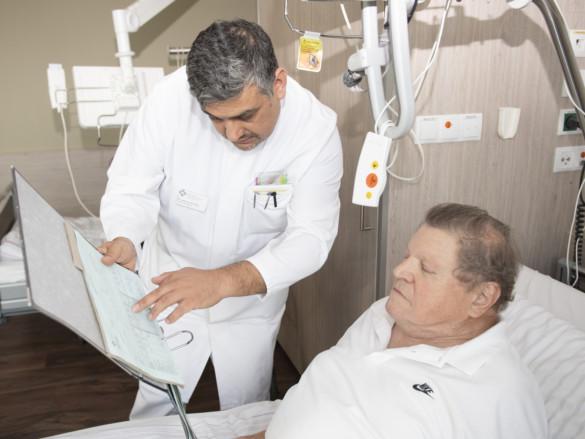 Chefarzt Dr. Gündug erläutert einem Patienten am Krankenbett seine Unrtersuchungsergebnisse.