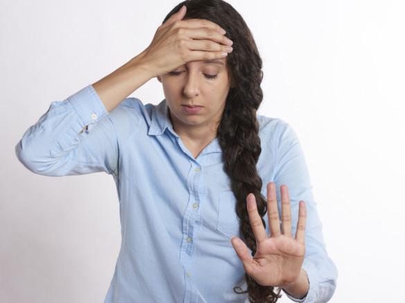 Eine junge Frau hält sich mit geschlossenen Augen den Kopf.