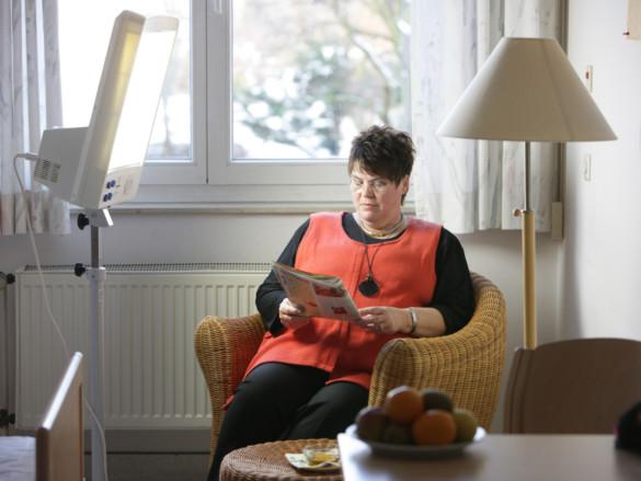 Eine Patientin der Klinik für Psychiatrie, Psychotherapie und Psychosomatik sitzt in einem Sessel bei der Lichttherapie.