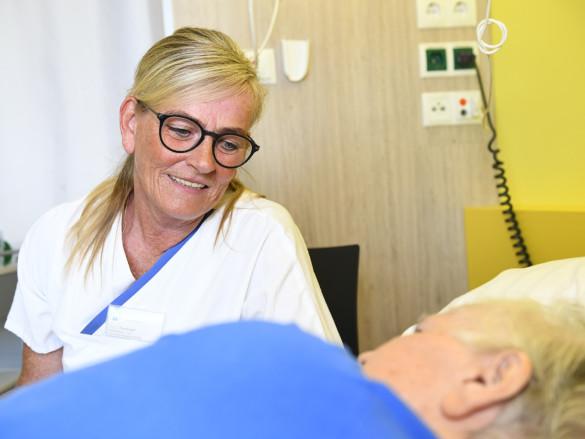 Pflegeassistentin Ellen Tenhaef spricht freundlich mit einer Patientin, die im Bett liegt.