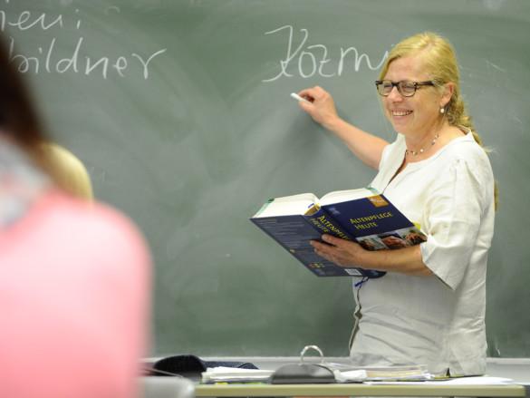Eine Dozentin des Fachseminars für Altenpflege schreibt an die Tafel.