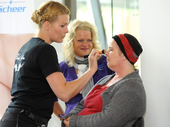 Brusttag in Kleve: Eine Kosmetikerin pudert und schminkt eine Besucherin.