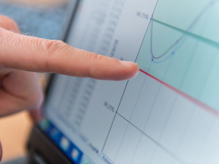 Erläuternde Hand zeigt auf einen Computerbildschirm mit einem Diagramm.