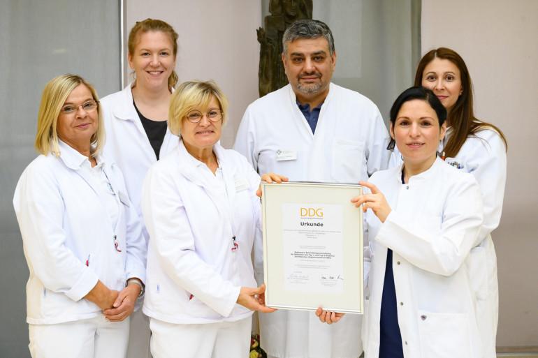 Das Team um Chefarzt Dr. Ufuk Gündug freut sich über die erfolgreiche Zertifizierung und präsentiert stolz das Zertifikat.
