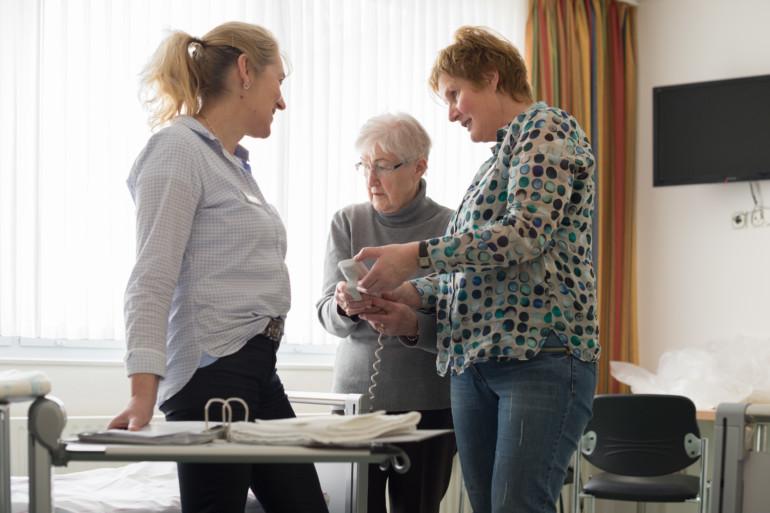 Annegret Janhsen und Viviane Bühne betreuen die Familie Pflege im Marienhospital Kevelaer. Im Bild mit einer Angehörigen, der sie die Funktion eines Pflegebettes erklären.
