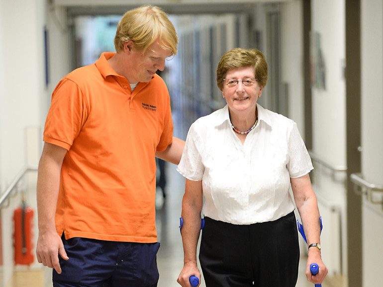 Ein Physiotherapeut unterstützt eine Patientin bei Gehübungen.