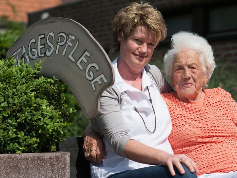 Tagespflege im Regina Pacis - Haus für Senioren. Eine Seniorin genießt mit einer Betreuerin die Sonne.