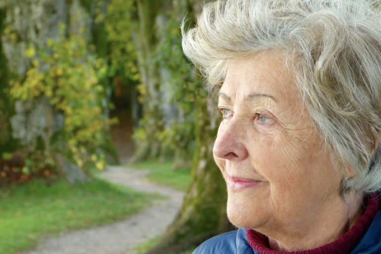 Eine Seniorin blickt in die Ferne.